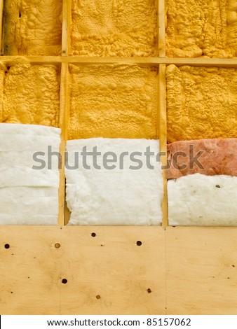 Different types of building insulation: polyurethane spray foam and fiberglass mats. - stock photo