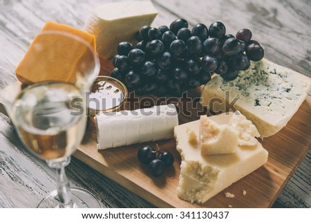 Different types of cheese with grape on wooden board served with the glass of white wine. Toned image - stock photo