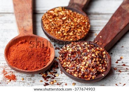 Different types of chilli flakes and paprika - stock photo