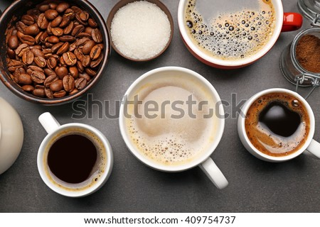 Different types of coffee in cups on dark table, top view - stock photo