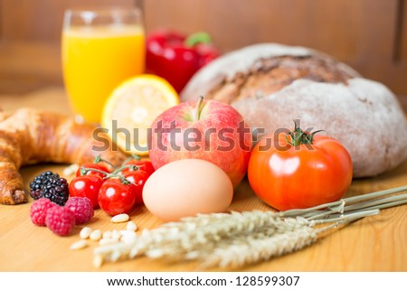 Different types of food such as bread, a tomato, apple, pine seeds, raspberry and a croissant as well a glass of orange juice - stock photo