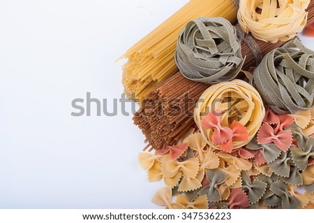 Different types of italian pasta. Whole spaghetti, farfalle pasta and pasta fettuccine nests isolated on white background - stock photo