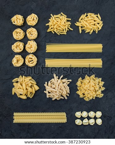 Different types of Italian uncooked pasta on black slate stone background, top view, vertical  - stock photo