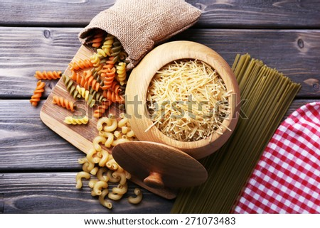Different types of pasta in containers on wooden background - stock photo