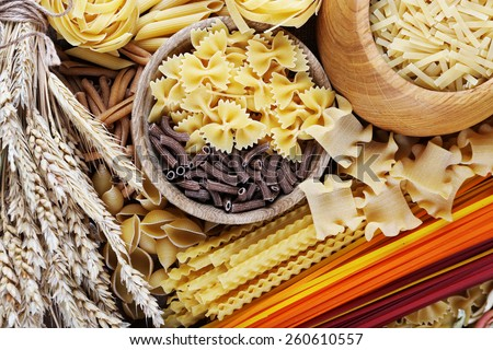 Different types of pasta with wooden utensil, macro view - stock photo