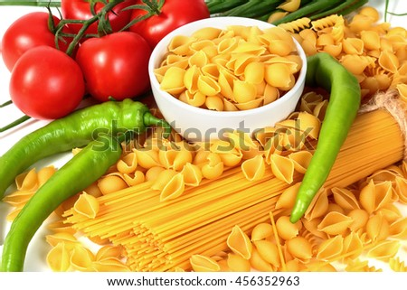Different types of raw Italian pasta with tomatoes and other vegetables. Top view background. - stock photo