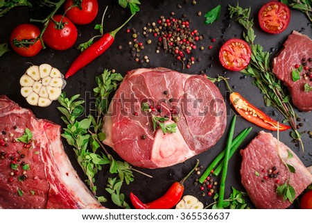 Different types of steaks set. Assorted raw meat on a black chalk board background. Rib eye steak on the bone, veal shank (ossobuco), fillet with cherry tomatoes, hot pepper and herbs.  - stock photo