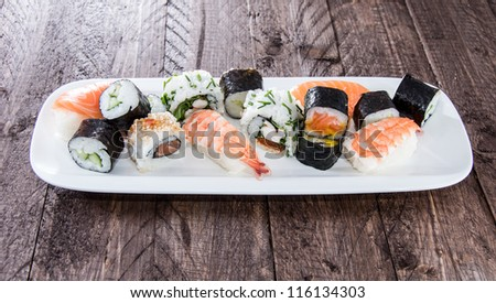 Different types of Sushi on a plate against wooden background - stock photo