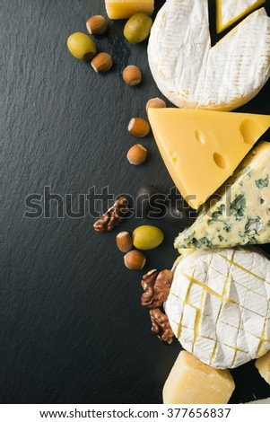 Different varieties of cheese on a black board. - stock photo