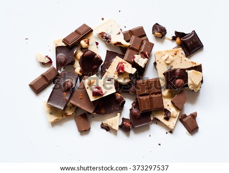 Different varieties of chocolate. White chocolate with hazelnuts and cranberries, milk and dark chocolate with hazelnuts isolated on white. - stock photo