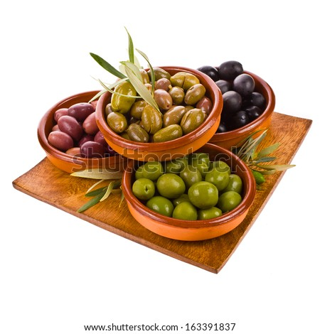 different varieties of olives marinated in traditional clay bowls decorated with branches of olive tree isolated on white background - stock photo