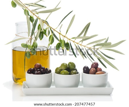 different varieties of olives marinated in white bowls and twig  of olive tree, jar of olive oil isolated on white - stock photo