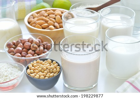 Different vegan milks on a table. Hazelnut, rice, soya and almond milk. Substitute for dairy milk. - stock photo