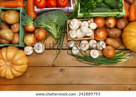 Different vegetables in boxes on wooden background top view - stock photo