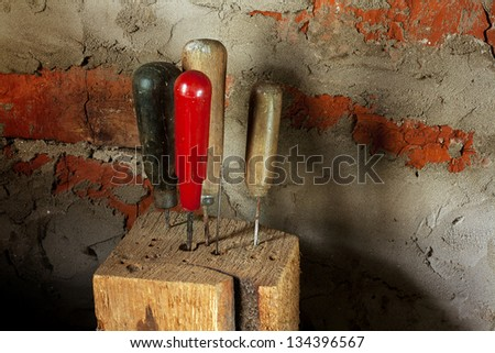 different vintage used awls in wooden ingot in workshop - stock photo