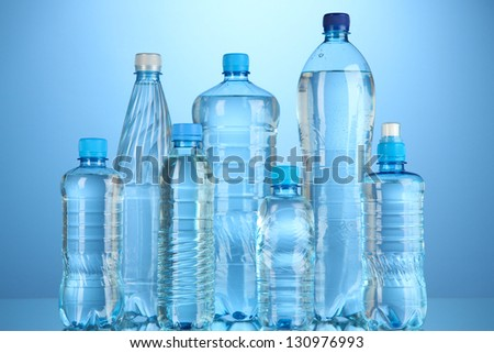 Different water bottles on blue background - stock photo