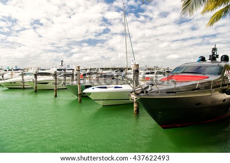 Different yachts in miami marina bay at south beach on water in bay at sunny day with clouds on blue sky - stock photo