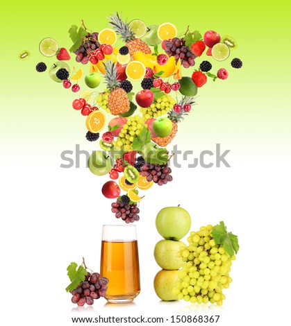Diffferent fruits and berries falls into glass of fresh juice, on green background - stock photo