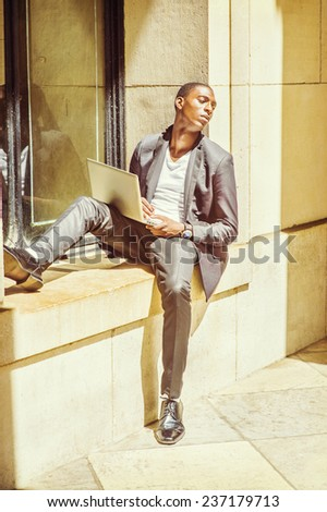 Difficult Task. Dressing in fashionable jacket, pants, leather shoes, a young black college student is sitting against a window frame, looking away, sad, thinking, working on a laptop computer.  - stock photo