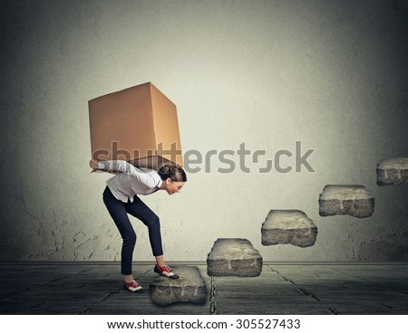 Difficult task perspective concept. Young slim woman carrying large heavy box on her back upstairs  - stock photo