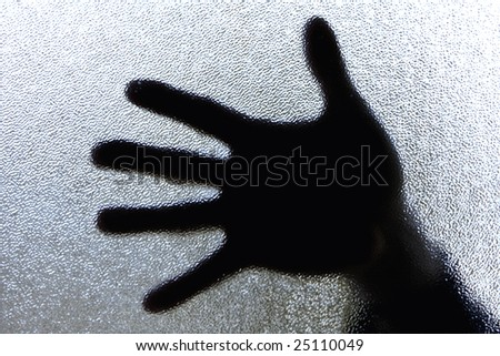 Diffuse image of a hand against glass - stock photo