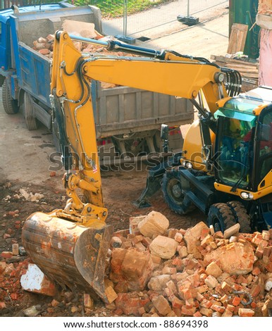Digger and Truckload of Rubble in House Under Demolition - stock photo