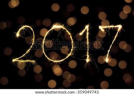 digit 2017 written with Sparkle firework on bokeh background - stock photo