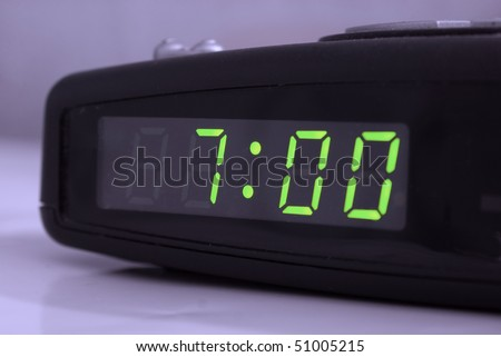 Digital alarm clock with green digits showing seven oclock - stock photo