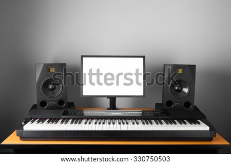 digital audio workstation (daw) studio with electronic piano and monitor speakers - stock photo