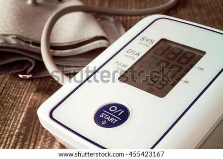 Digital blood pressure monitor on wooden background - stock photo