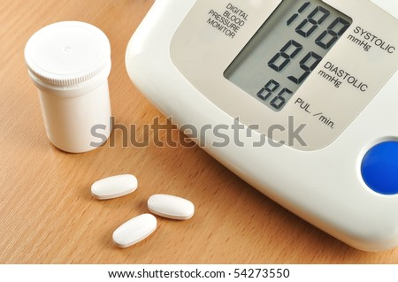 digital blood pressure monitor with tablets - stock photo