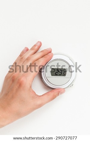 digital climate thermostat controlling by hand - stock photo
