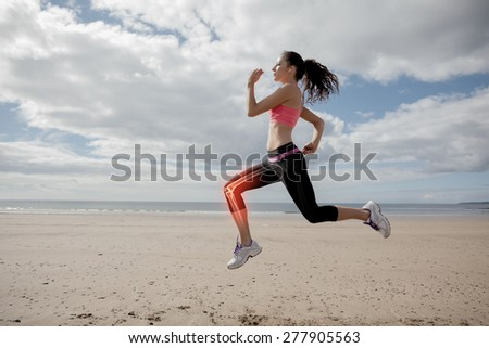 Digital composite of Highlighted leg bones of jogging woman on beach - stock photo
