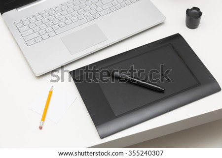 digital drawing tablet and laptop on the table - stock photo