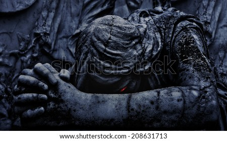 Digital edited and manipulated close up photo of a marble statue of an angel praying with evil eyes expression  - stock photo
