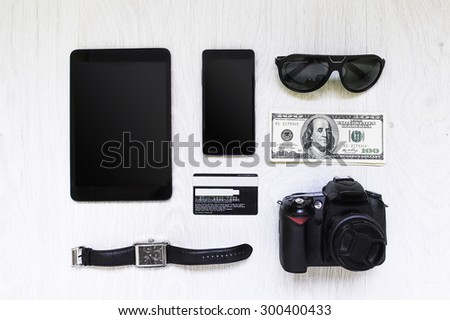 digital gadgets on the wooden table top view, money, watches, photo camera, phone, tablet, glasses, Credit Card, Passport, dollars - stock photo