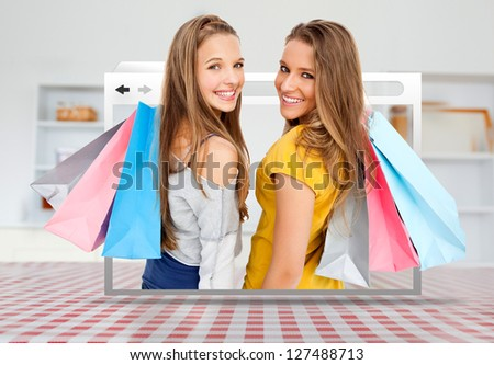 Digital internet window showing girls with shopping bags open on kitchen table - stock photo
