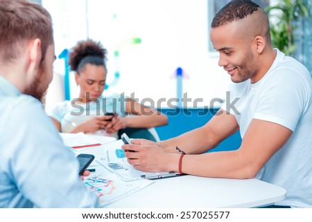 Digital natives. Young creative people messaging with their smartphones while in the meeting room - stock photo