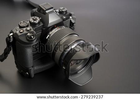 Digital photo camera in black background - stock photo