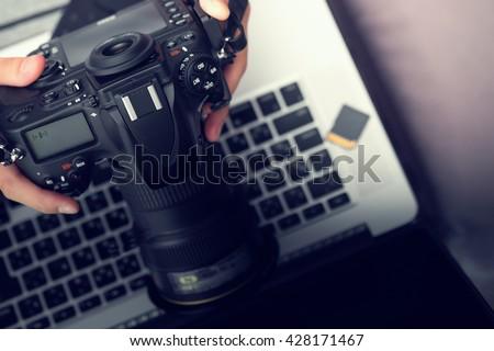 Digital Photography Workstation. Modern Digital DSLR Camera, Laptop Computer and Display. - stock photo