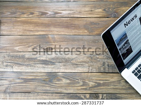 Digital subscription on rough wooden desk concept. Handcrafted natural wooden texture table with large copy space and cropped laptop with world news page on screen - stock photo