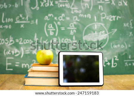 Digital tablet and apple on the desk in front of blackboard - stock photo