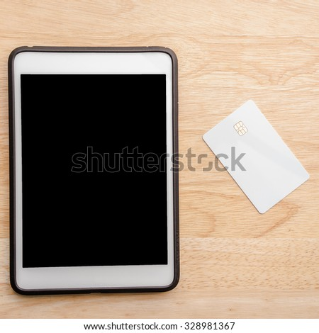 Digital tablet and blank white credit card on table. Business online everywhere. - stock photo