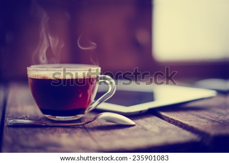 Digital tablet  and cup of coffee on old wooden desk. Simple workspace or coffee break in morning/ selective focus - stock photo