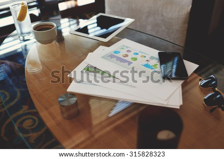 Digital tablet and mobile phone with blank copy space screen for your advertising content or text message, paper documents with charts on a glass table in modern coffee shop - stock photo