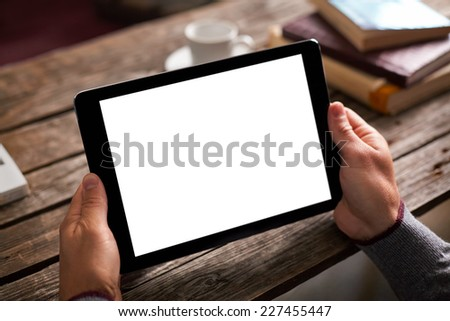 Digital tablet computer with isolated screen in male hands over cafe background - table, cup of coffee... - stock photo