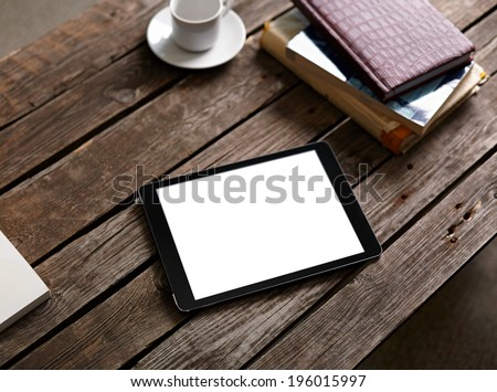 Digital tablet computer with isolated screen on wooden table with cup of coffee - stock photo