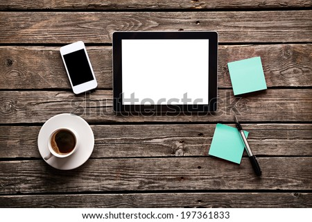 Digital tablet computer with sticky note paper and cup of coffee on old wooden desk. Simple workspace or coffee break with web surfing. - stock photo