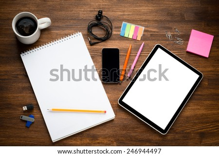 Digital tablet computer with sticky note paper and cup of coffee, smart phone on old wooden desk. Simple workspace or coffee break with web surfing. - stock photo