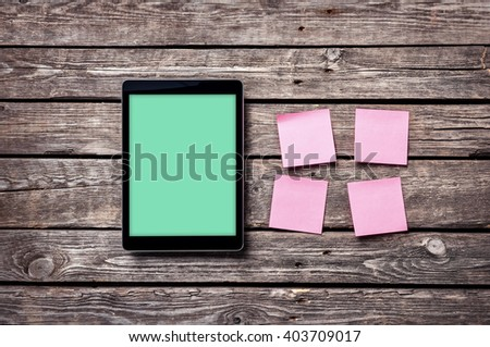 Digital tablet computer with sticky notes on wooden desk. Clipping path for display included. - stock photo